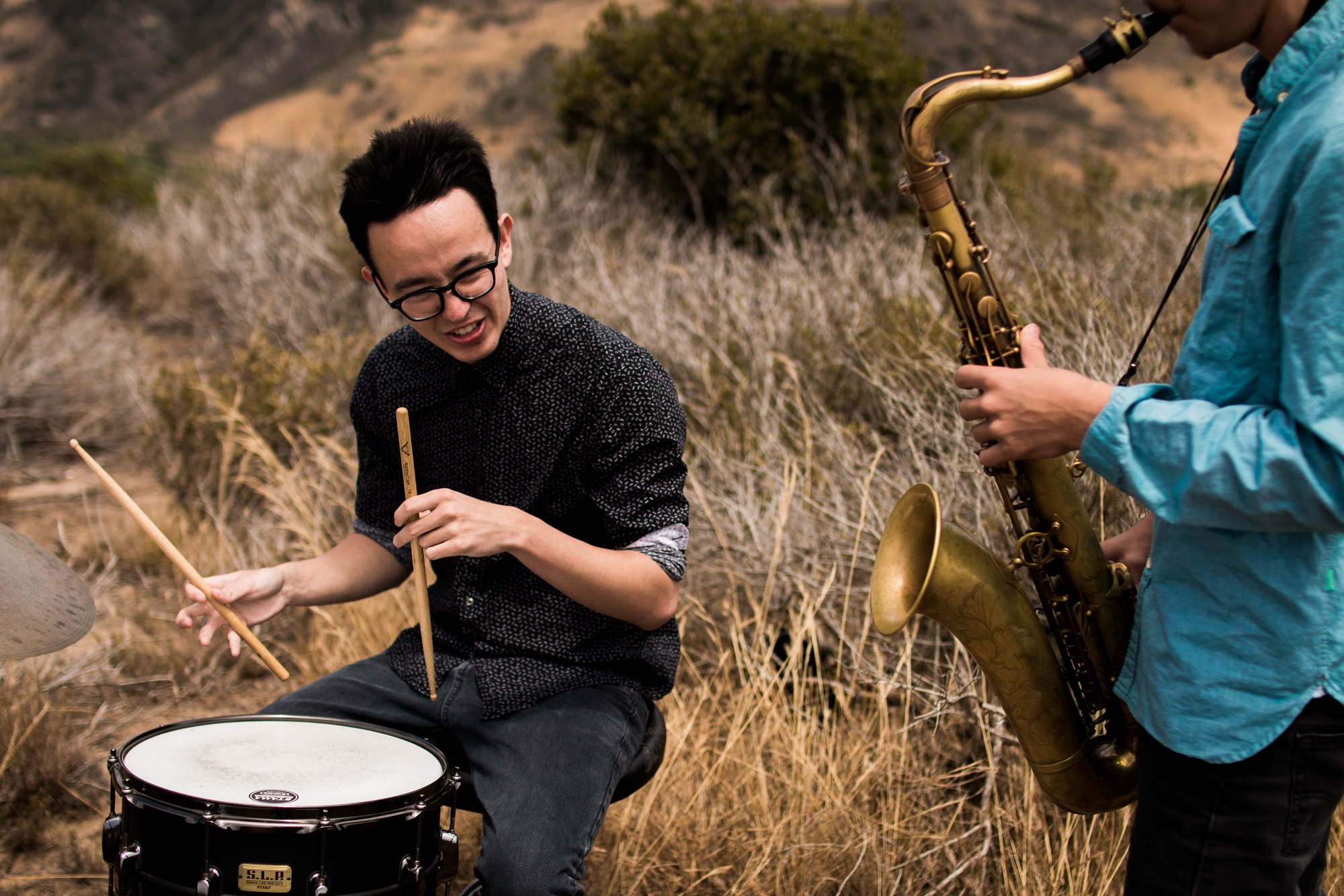 Photo of men playing drum and sax in a field by Cole Hutson