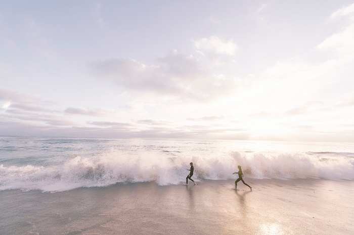 Photo of two people in the surf by Frank McKenna